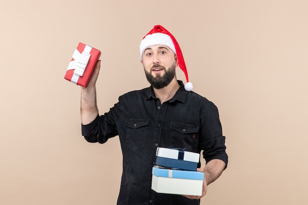 Widok z przodu młodego mężczyzny trzymającego prezenty świąteczne na różowej ścianie