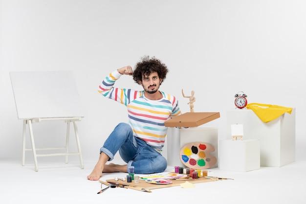 Widok z przodu młodego mężczyzny trzymającego pudełko pizzy na białej ścianie