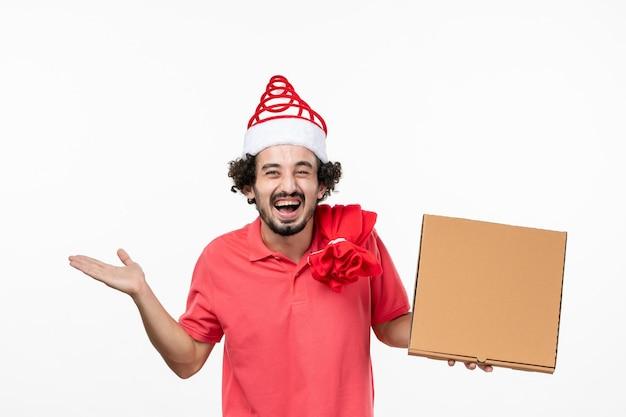 Widok z przodu młodego mężczyzny trzymającego pudełko z dostawą żywności na białej ścianie