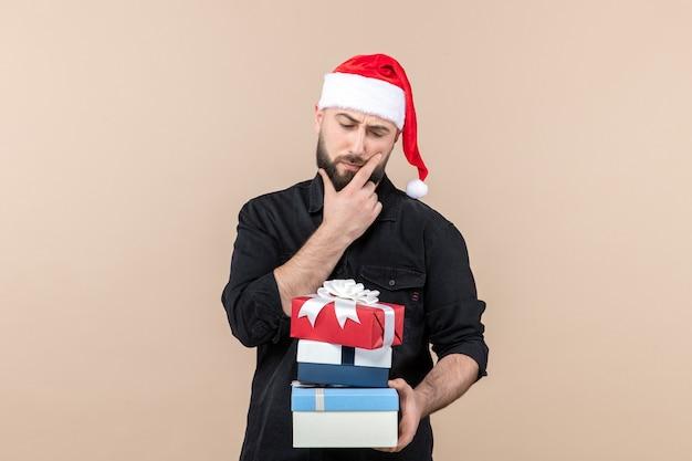 Widok z przodu młodego mężczyzny trzymającego świąteczne prezenty na różowej ścianie