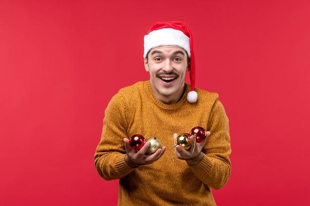 Widok z przodu młodego mężczyzny trzymającego zabawki choinkowe na czerwonej ścianie