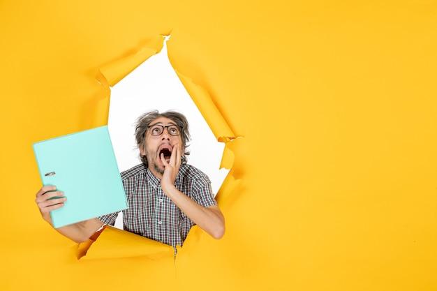 Widok z przodu młodego mężczyzny trzymającego zielony plik na żółtej ścianie