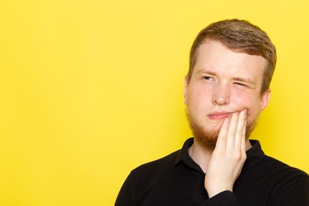 Widok z przodu młodego mężczyzny w czarnej koszuli, pozowanie i ból zęba