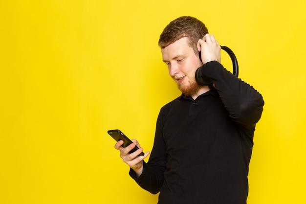 Widok z przodu młodego mężczyzny w czarnej koszuli słuchania muzyki przez słuchawki z uśmiechem
