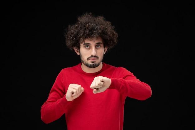 Widok z przodu młodego mężczyzny w czerwonej koszuli na czarnej ścianie