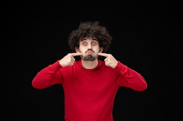 Widok z przodu młodego mężczyzny w czerwonym swetrze na czarnej ścianie