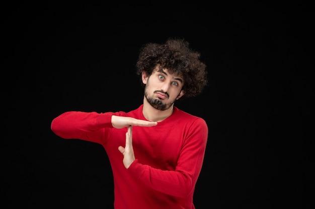 Widok z przodu młodego mężczyzny w czerwonym swetrze pokazującym literę t na czarnej ścianie