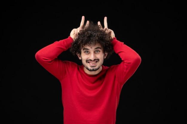 Widok z przodu młodego mężczyzny w czerwonym swetrze uśmiecha się na czarnej ścianie