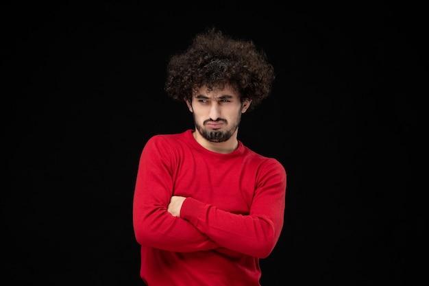 Widok z przodu młodego mężczyzny w czerwonym swetrze z szaloną twarzą na czarnej ścianie
