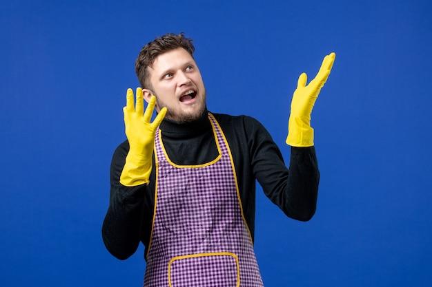 Widok z przodu młodego mężczyzny w fartuchu stojącego na niebieskiej ścianie