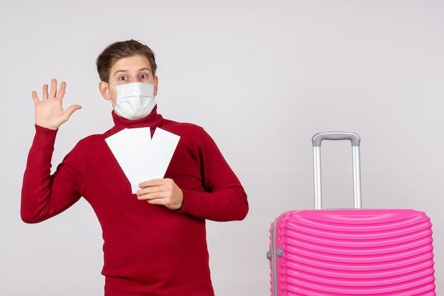 Widok z przodu młodego mężczyzny w masce, trzymając bilety lotnicze na białej ścianie