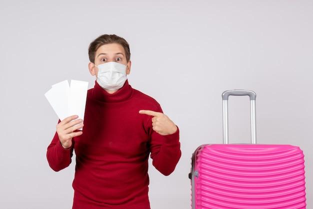 Widok z przodu młodego mężczyzny w masce, trzymając bilety na białej ścianie