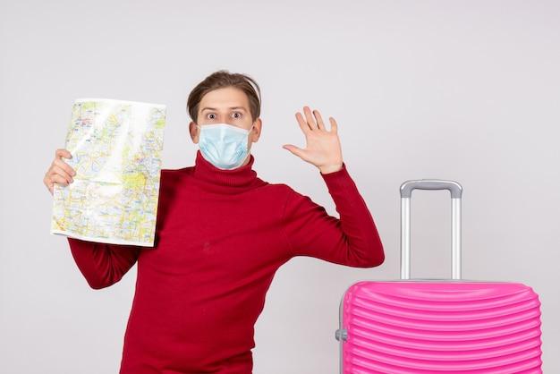 Widok z przodu młodego mężczyzny w masce trzymającej mapę miasta na białej ścianie