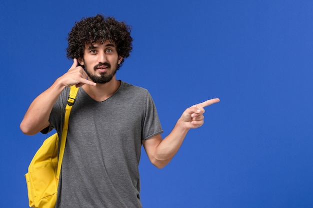 Widok z przodu młodego mężczyzny w szarej koszulce na sobie żółty plecak, pozowanie na niebieskiej ścianie