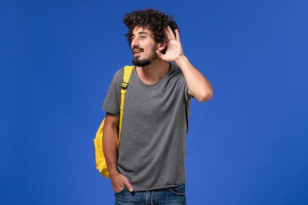 Widok z przodu młodego mężczyzny w szarej koszulce w żółtym plecaku, który próbuje usłyszeć na niebieskiej ścianie