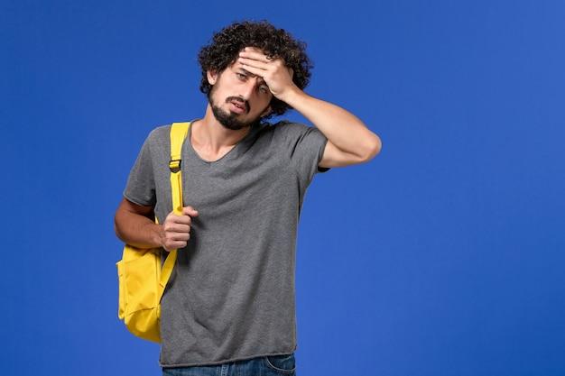 Widok z przodu młodego mężczyzny w szarej koszulce w żółtym plecaku na niebieskiej ścianie