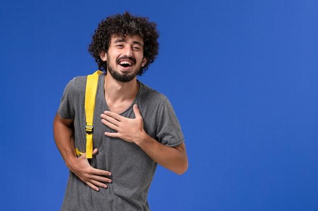 Widok z przodu młodego mężczyzny w szarej koszulce w żółtym plecaku, śmiejącego się na niebieskiej ścianie