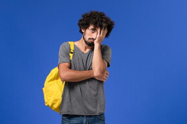 Widok z przodu młodego mężczyzny w szarym t-shircie ubrany w żółty plecak przygnębiony na niebieskiej ścianie