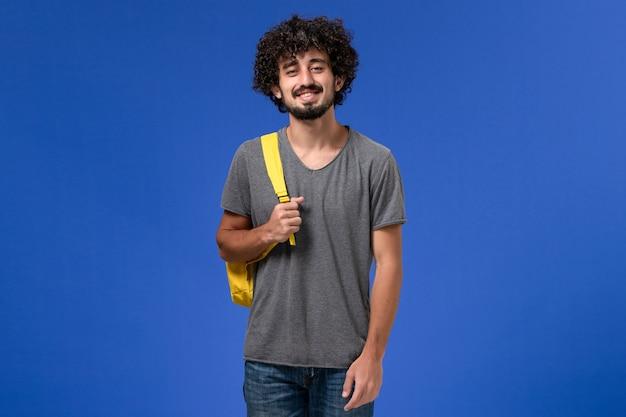 Widok z przodu młodego mężczyzny w szarym t-shircie ubrany w żółty plecak uśmiechnięty na niebieskiej ścianie