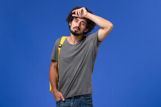 Widok z przodu młodego mężczyzny w szarym t-shircie w żółtym plecaku pozującym na niebieskiej ścianie