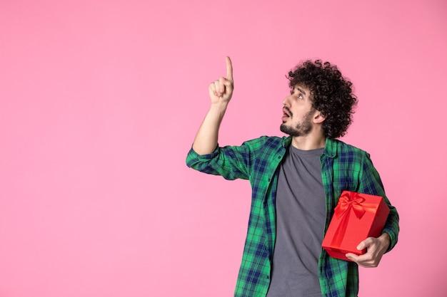 Widok z przodu młodego mężczyzny z czerwonym opakowaniem na jasnoróżowej ścianie