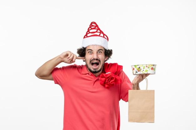 Widok z przodu młodego mężczyzny z dostawą jedzenia na białej ścianie
