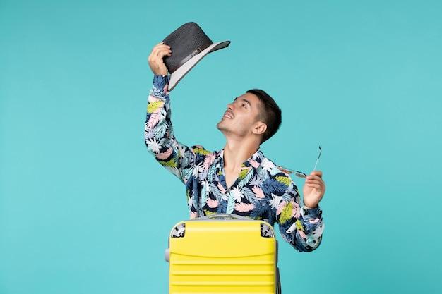 Widok z przodu młodego mężczyzny z jego żółtą torbą przygotowuje się do długiej podróży na jasnoniebieskiej ścianie