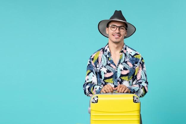 Widok z przodu młodego mężczyzny z jego żółtą torbą przygotowuje się do podróży i uśmiecha się na niebieskiej ścianie