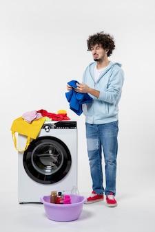 Widok z przodu młodego mężczyzny z pralką i brudnymi ubraniami na białej ścianie