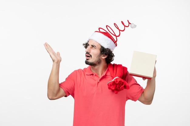 Widok z przodu młodego mężczyzny z prezentem świątecznym na białej ścianie