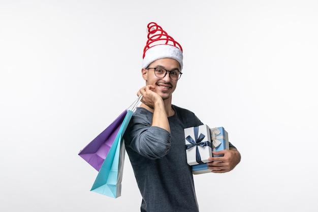 Widok z przodu młodego mężczyzny z świątecznymi prezentami na białej ścianie