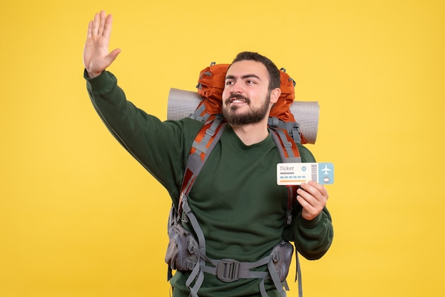 Widok z przodu młodego uśmiechniętego podróżującego faceta z plecakiem i pokazującym bilet na żółtym tle