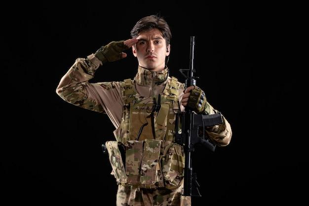 Widok z przodu młodego żołnierza salutującego w mundurze na czarnej ścianie