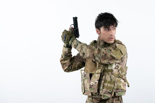 Widok z przodu młodego żołnierza w kamuflażu z białą ścianą pistoletu