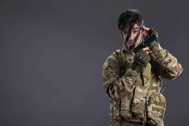 Widok z przodu młodego żołnierza w kamuflażu z pistoletem na ciemnej ścianie
