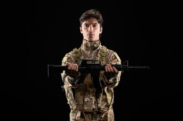 Widok z przodu młodego żołnierza w mundurze trzymającego karabin na czarnej ścianie