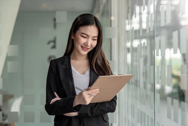 Widok z przodu młodej bizneswoman azjatyckiej stojącej trzymającej dokument obok dużego lustra w biurze.