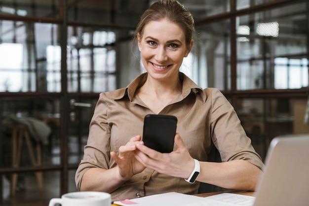 Widok z przodu młodej bizneswoman przy użyciu swojego smartfona podczas spotkania