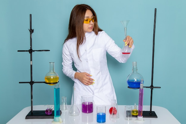 Widok z przodu młodej chemik kobiet w białym garniturze przed stołem pracującym z roztworami