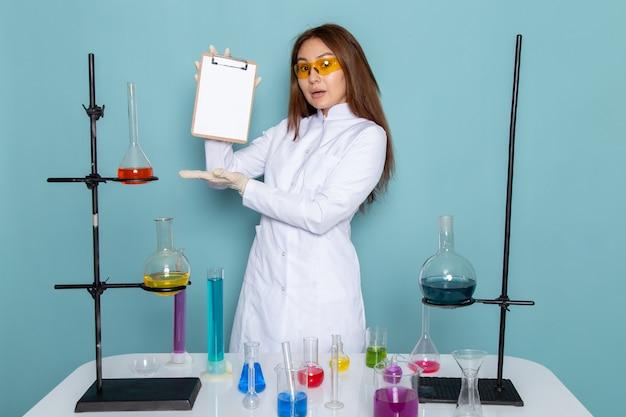 Widok z przodu młodej chemik kobiet w białym garniturze przed stołem trzymając notatnik
