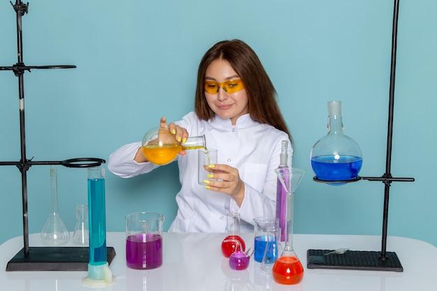 Widok z przodu młodej chemik kobiet w białym kolorze przed stołem do pracy z roztworami i uśmiechnięte