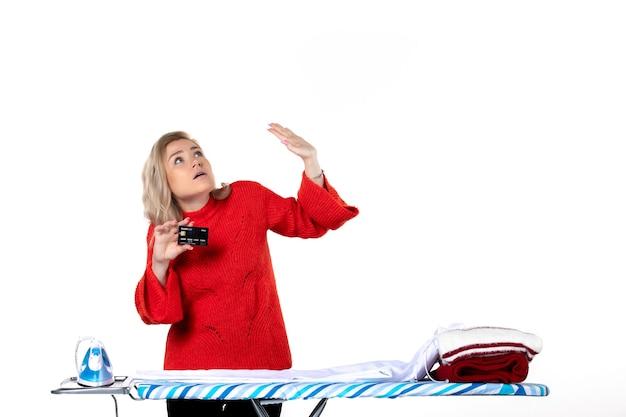 Widok z przodu młodej ciekawej atrakcyjnej kobiety stojącej za deską do prasowania pokazującą kartę bankową patrzącą w górę po lewej stronie na białym tle