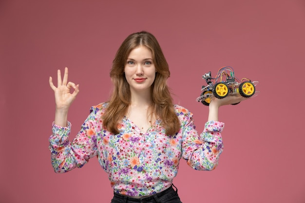 Widok z przodu młodej damy pokazuje, że lubi zabawkę samochodową