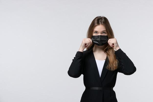 Widok z przodu młodej damy w garniturze, noszącej maskę chirurgiczną i pozującej do kamery na białym tle