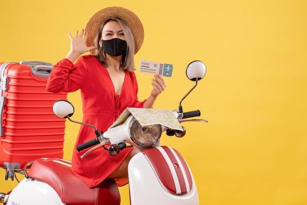 Widok z przodu młodej damy z czarną maską na motorowerze trzymając bilet macha ręką