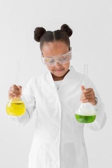 Widok z przodu młodej dziewczyny naukowca w fartuchu gospodarstwa mikstury w probówkach