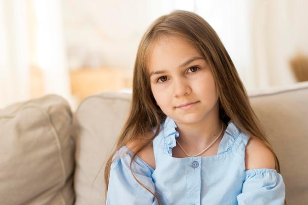 Widok z przodu młodej dziewczyny, pozowanie w domu na kanapie