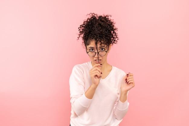 Widok z przodu młodej kobiety bawiącej się włosami na różowej ścianie