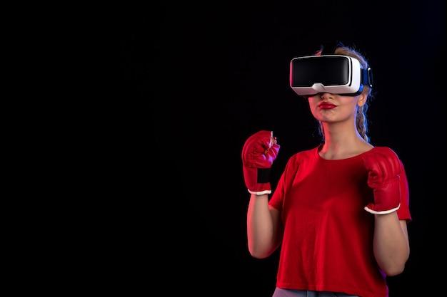 Widok z przodu młodej kobiety grającej w vr w rękawiczkach mma na ciemnej wizualnej fantazji d