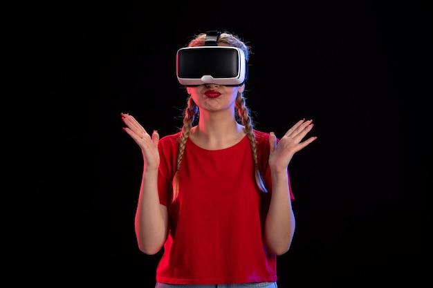 Widok z przodu młodej kobiety grającej w wirtualną rzeczywistość na ciemnej ścianie